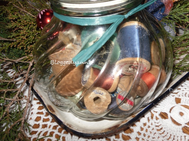 Old wooden thread spools in a jar